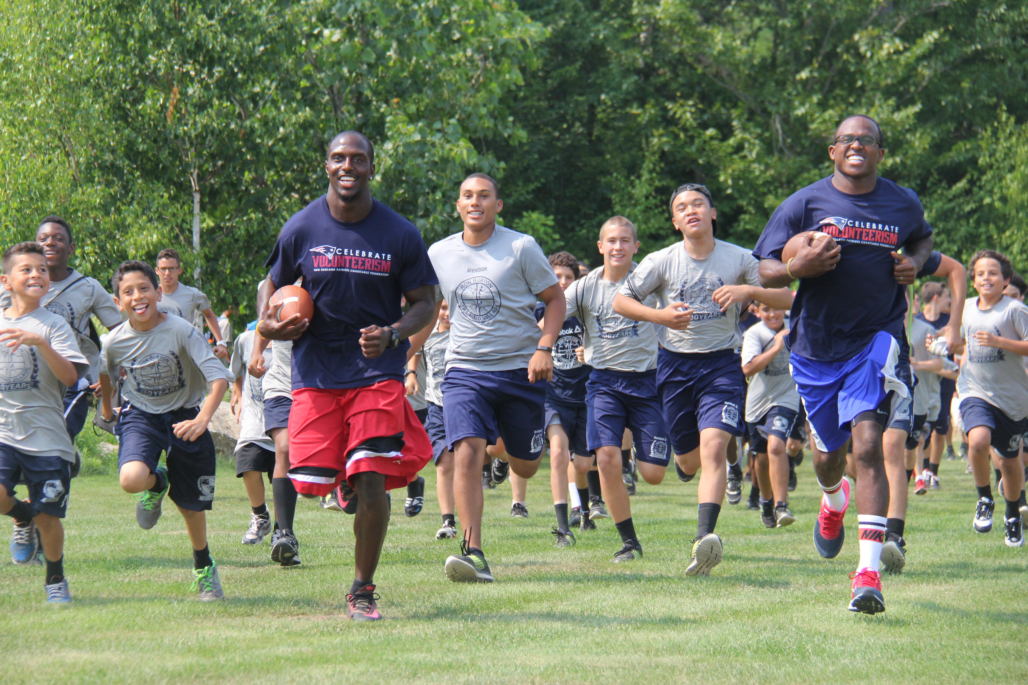 "McCourty and special teams captain Matthew Slater leading campers from the Ron Burton Training Village out to the field for ""NFL Combine"" themed activities."
